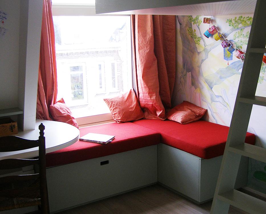 Onder de bank zitten grote lades; ideaal voor een kleine kamer als deze